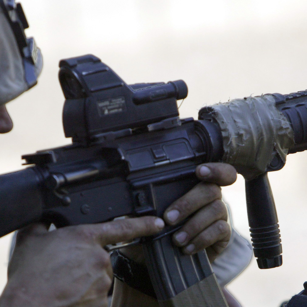 Armed Forces Serviceman Shooting through a Red Dot Sight